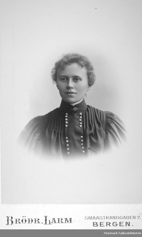 Portrett av en dame kledt i en mørk overdel/bluse. Lyse/blanke knapper går tett-i-tett fra halsen og nedover brystet. Portrettet er tatt hos Brødrene Larm i Bergen.