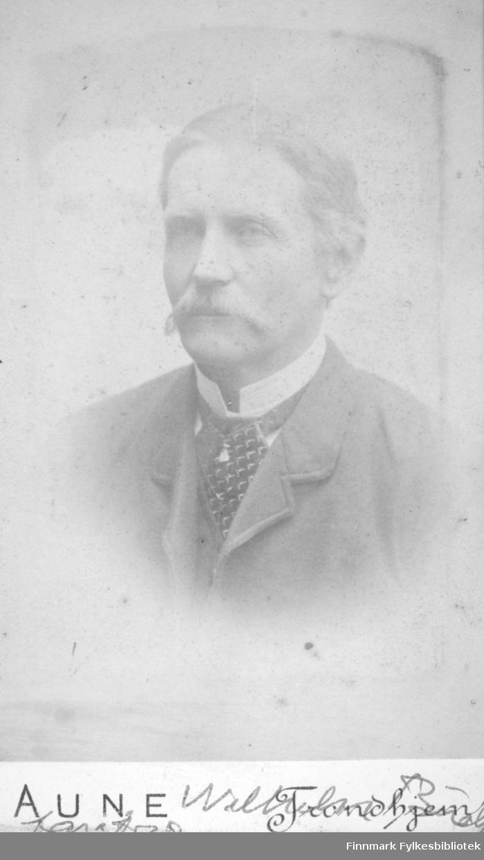Portrett av en mann i en ganske mørk dressjakke, hvit skjorte og mønstret slips.