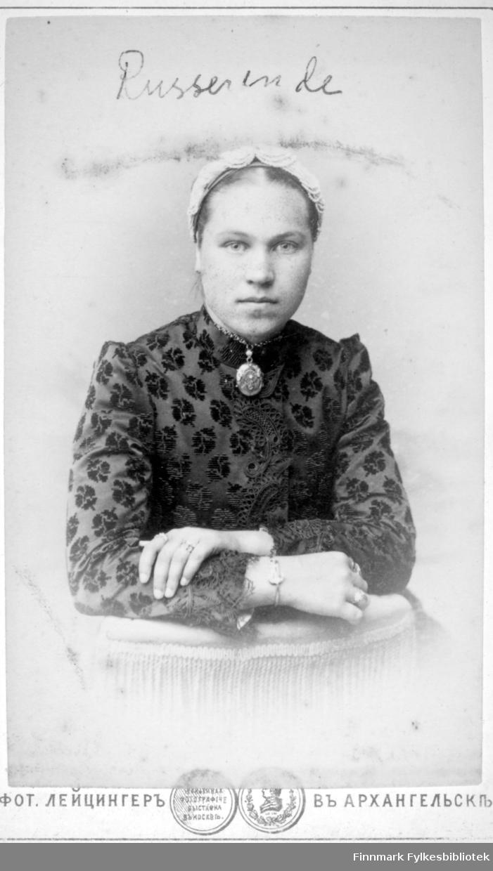 Portrett av en russisk dame. Hun har en mørk, mønstret bluse og en lys kyse på hodet. Rundt halsen henger en stor brosje. Hun har et armbånd rundt handleddet og ringer på fingrene.