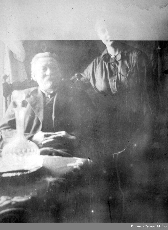 Arthur Buck sitter i en stol med høy rygg og kona hans, Kirsten Buck, står rett bak han. Han har en ganske mørk dress med skjorte og slips på seg. Hun har en mørk bluse med noe pynt i halsen. Sofaen de sitter i er mørk med ganske høy rygg og veggen bak er lys. Lyset skinner gjennom et vindu til høyre for dem og en del av en lys gardin ses. Et bord stå rett foran mannen og har en mønstret duk på. En blomstervase eller en karafel står på bordet rett foran dem.