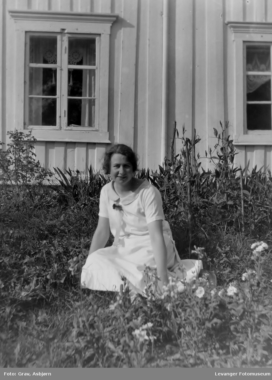 Kvinne i lys kjole sitter foran hus.