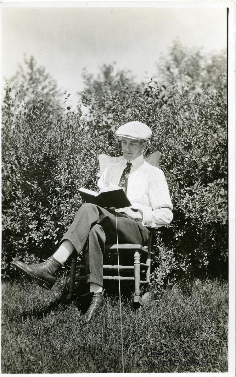 Mann som sitter i en gyngestol og leser. Han sitter ute, tett opp til noen busker. Dette er et postkort