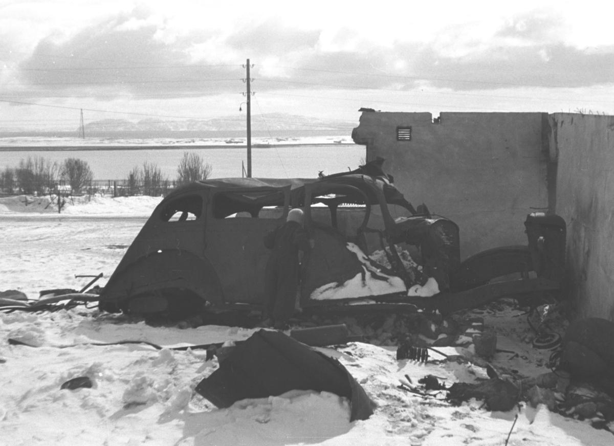 En person står og ser inn i et bilvrak i nærheten av skolen i Vadsø. Rett før sjøen begynner, ligger kirkegården. I horisonten ses Vadsøya med luftmasta.