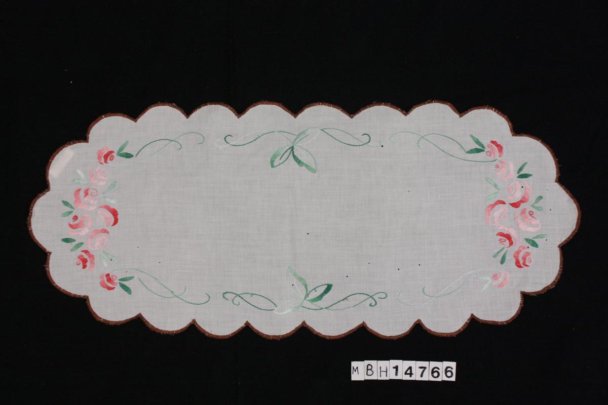 Rektangulær duk med bølgekant i hvit bomull. Plattsømbroderi: en brun konturstrek følger kanten, midten av duken har to felter med rød/rosa broderte roser og grønt bladverk.