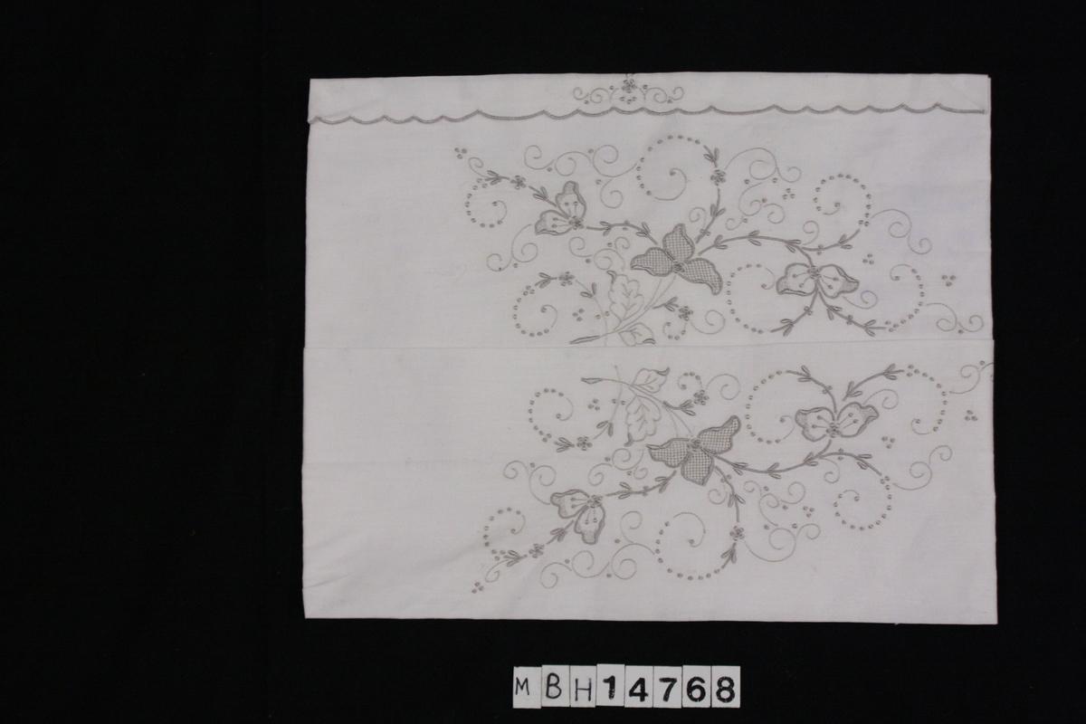 Hvit bomullstekstil brodert med grå/sølvfarget tråd. Slyngplanter og blomster brodert i kontursting. Tekstilet ser ikke ut til å være ferdig montert, delvis løse deler, er brettet flere ganger og har store tråklesting som holder deler delvis sammen.