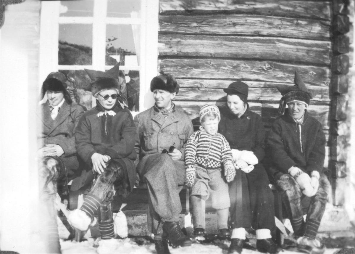 Tor Hauge sitter mellom sine foreldre, Leif og Alfrida, også kalt Frida . De to andre personene på benken, bor i området. Bildet er tatt i solveggen ved Alleknjarg fjellstue. Det er vinterstid, og snøen ligger på bakken