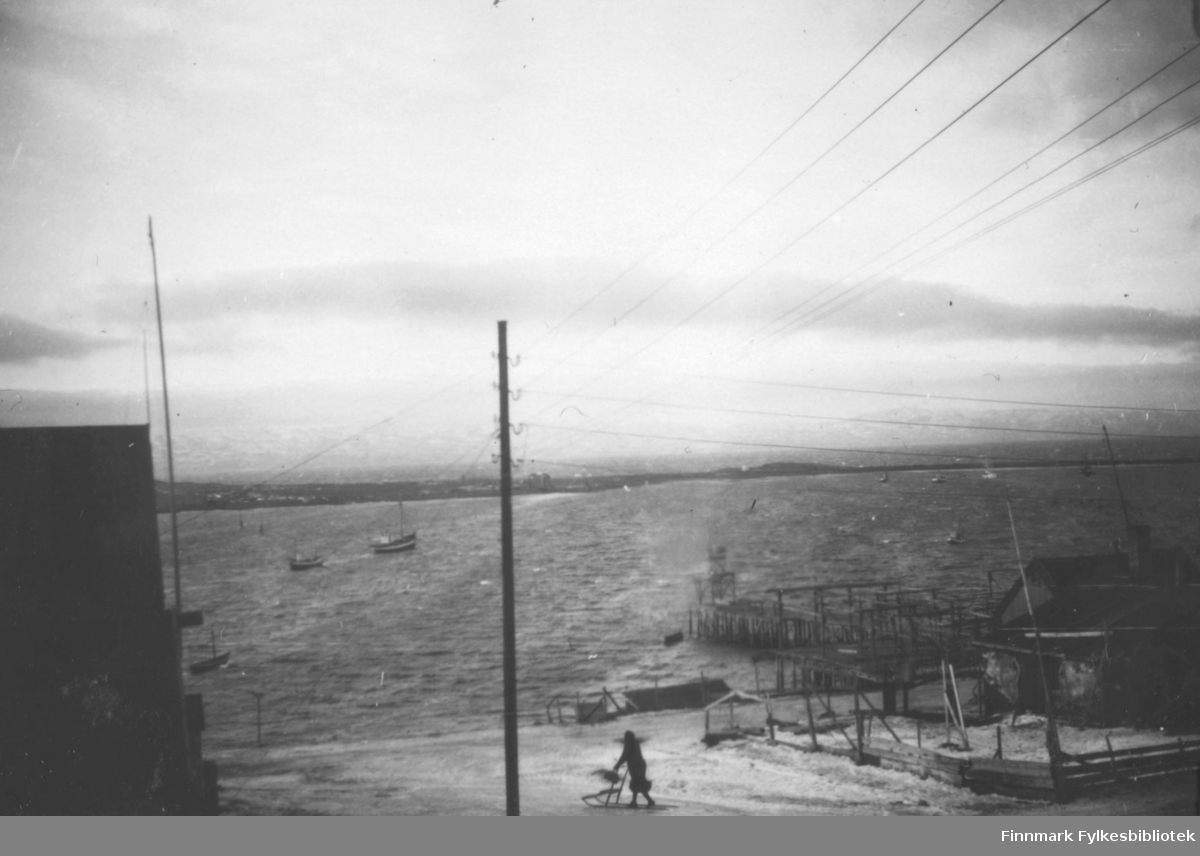 Mot øya, fra Hauge hus i Nyborgveien, der hvor nå Sildoljefabrikken ligger, Bekola kaia nede på Vadsø siden. dame på sparkstøtting sjø