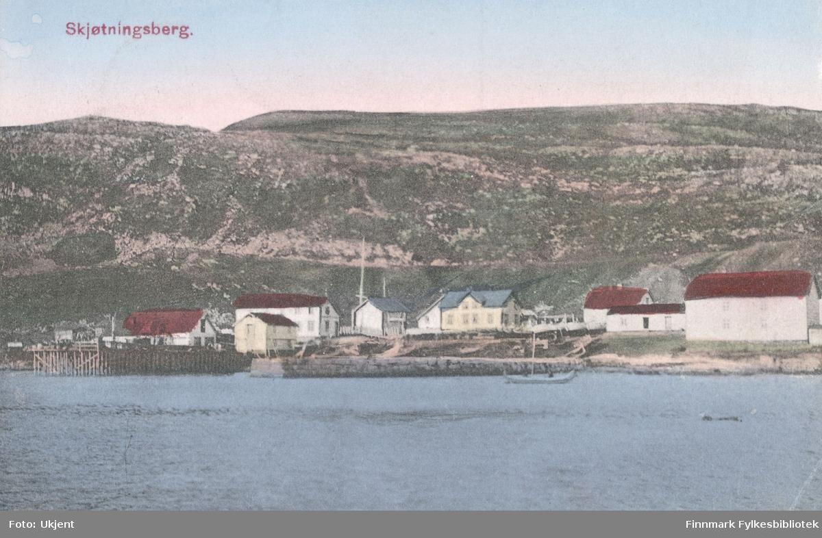 Et postkort med Skjøtningsberg som motiv. På bildet kan man se en havn med kai, båter, en mollo(?) og bygninger. I bakgrunnen kan man se fjell.