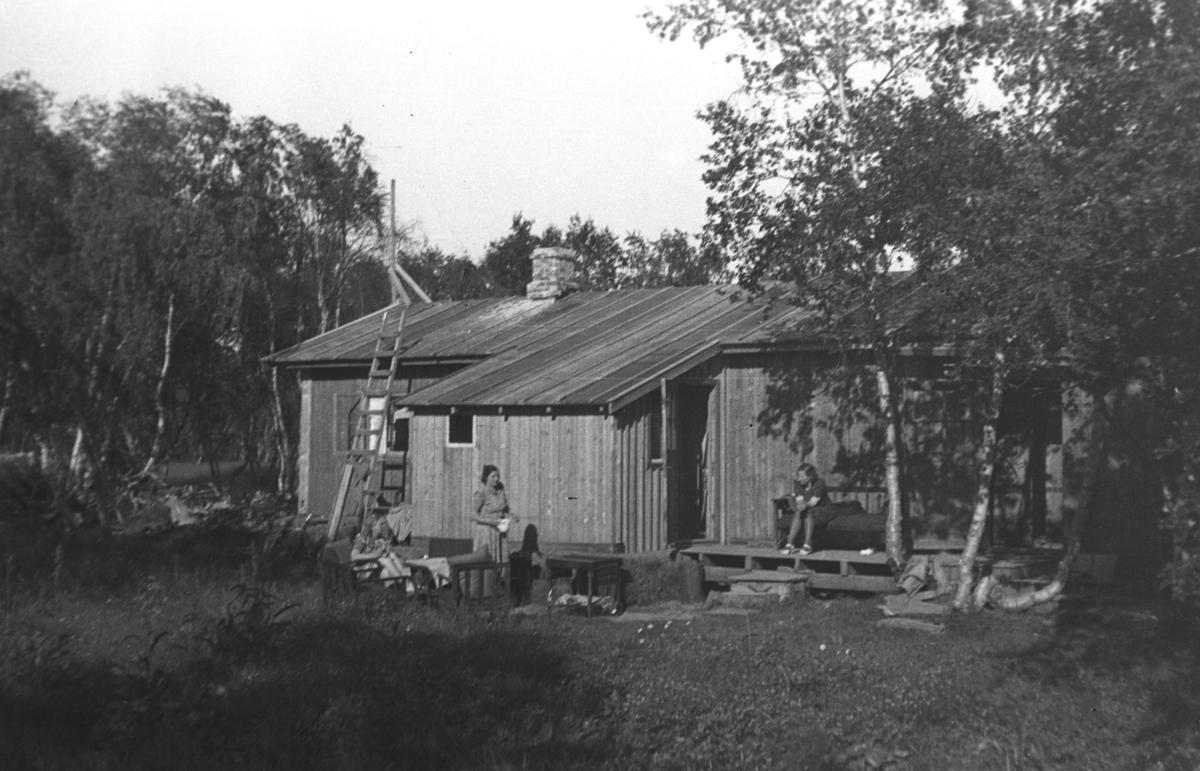 Tre kvinner utenfor et hus i skogen. Personer og sted er ukjent, men det kan være i Tana.