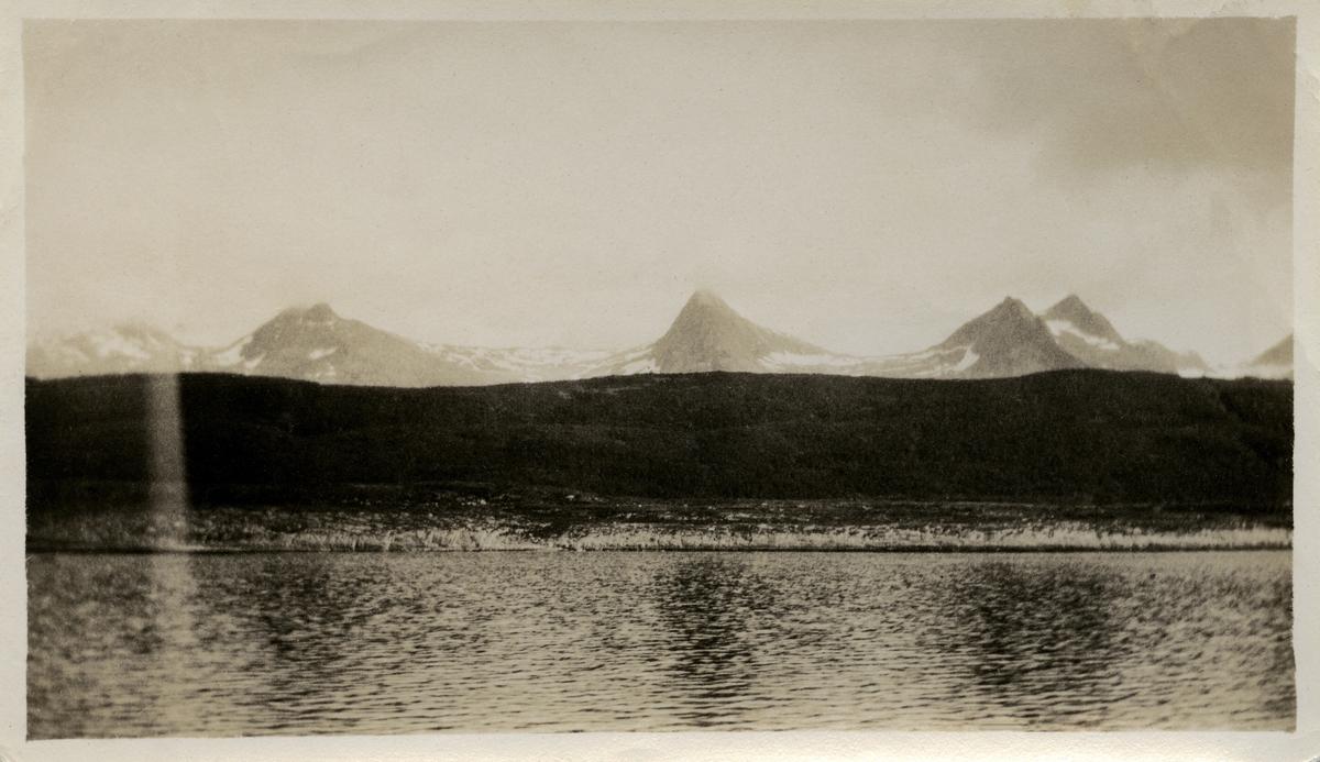 Tre ukjente snødekte fjelltopper, muligens tatt et sted i Nordland.