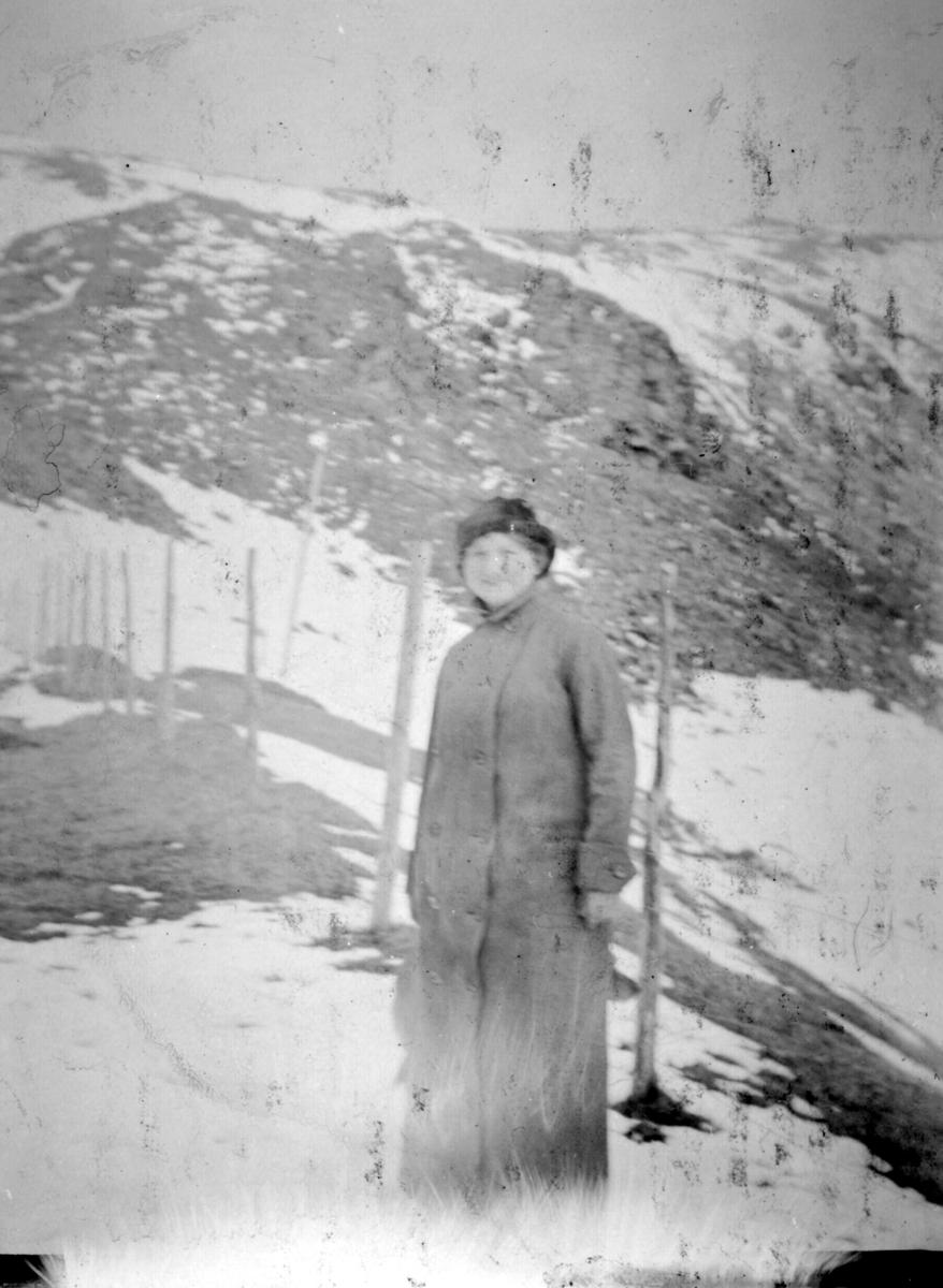 Sara Soelberg står ute kledd i kåpe og hatt. Bak henne kan man se snødekte fjell.