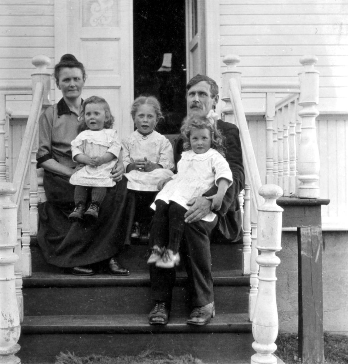 """""""I Bergsfjord. Onkel Hagbart og tante Anna. Hellgjerd (eldst), Annfrid og Nelly (yngst)."""" Barna i bildet er kledd i kjoler. Gruppen sitter på en trapp. Hagbart Hansen var fotografens bror, og Anna hans kone."""