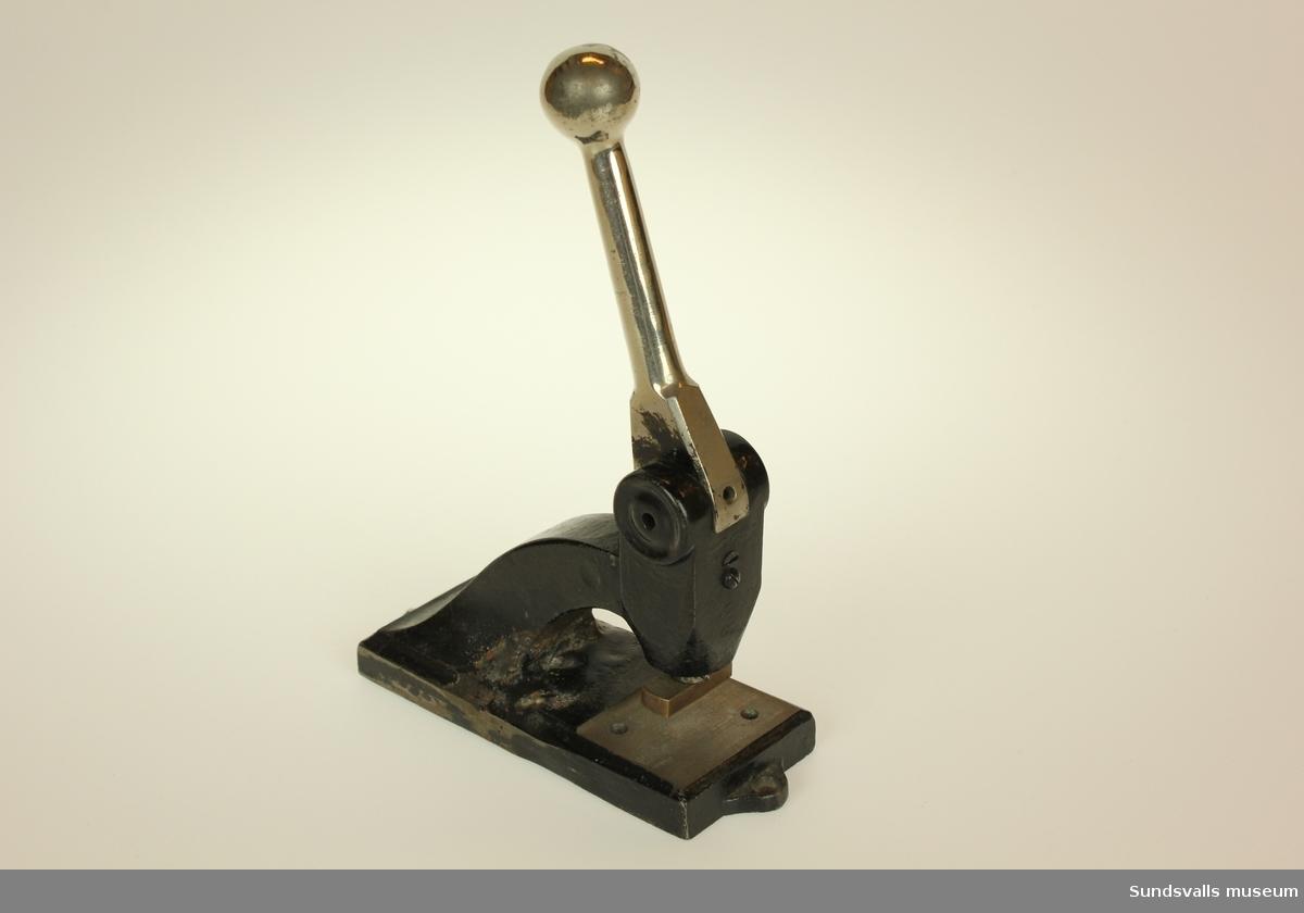 Svart gjutjärnsmaskin för prägling av företagslogotyp.