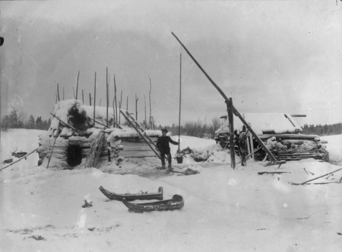 En mann i samedrakt står ved en brønn og holder i tauet som bøtta henger i. Han står foran en liten bygning, muligens et matlager. Bak til høyre står en annen liten bygning. I forgrunnen står to sleder/kjelker.