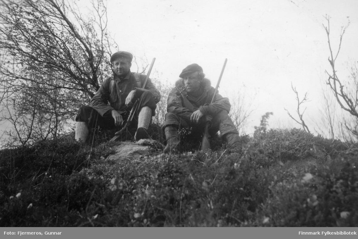 To jegere tar en pust i bakken med geværene hvilende i armkroken. Personer og sted er ukjent.