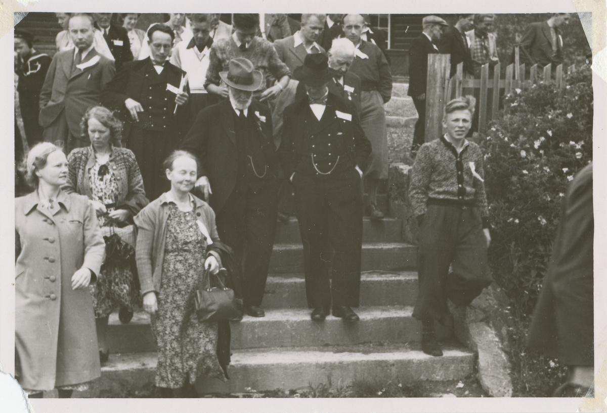 En forsamling mennesker på vei ned ei trapp etter en sammenkomst med ukjent formål. Mange har ei sløyfe festet på brystet.