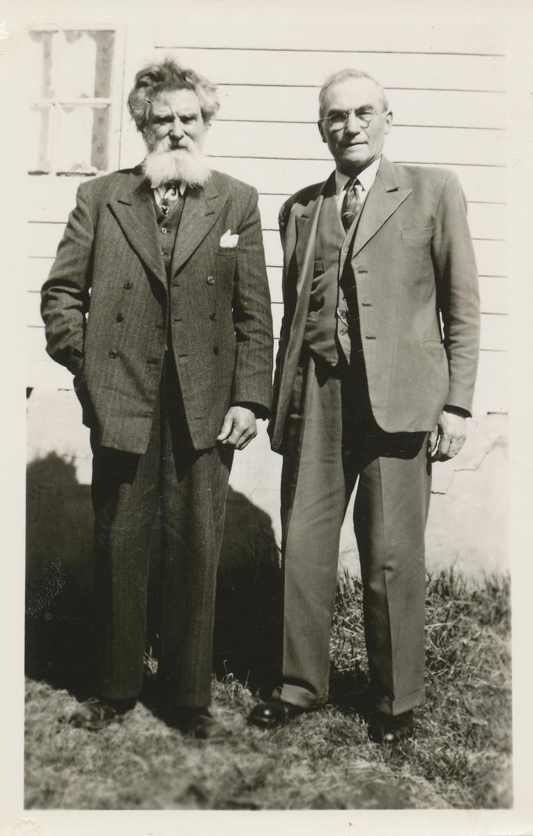 To menn poserer foran et hus.
