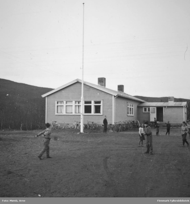 Boftsa skole, 1958. Barn leker i skolegården. Ved skolen kan man se flere sykler lent til veggen.