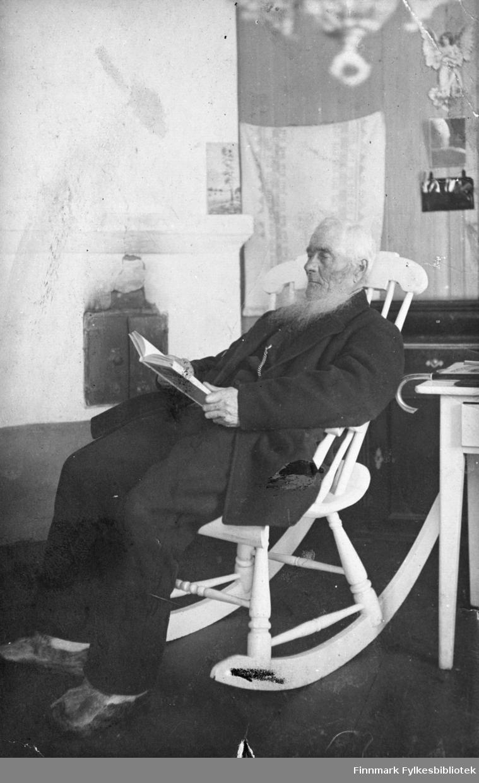 Predikant Oluf 'Olli' Koskamo fra Tana sitter på gyngestolen i stua foran peisen og leser bok. På veggen bak han henger en liten speil og en engelfigur (porselen?). På bordet ved siden av han ligg det en kjepp.
