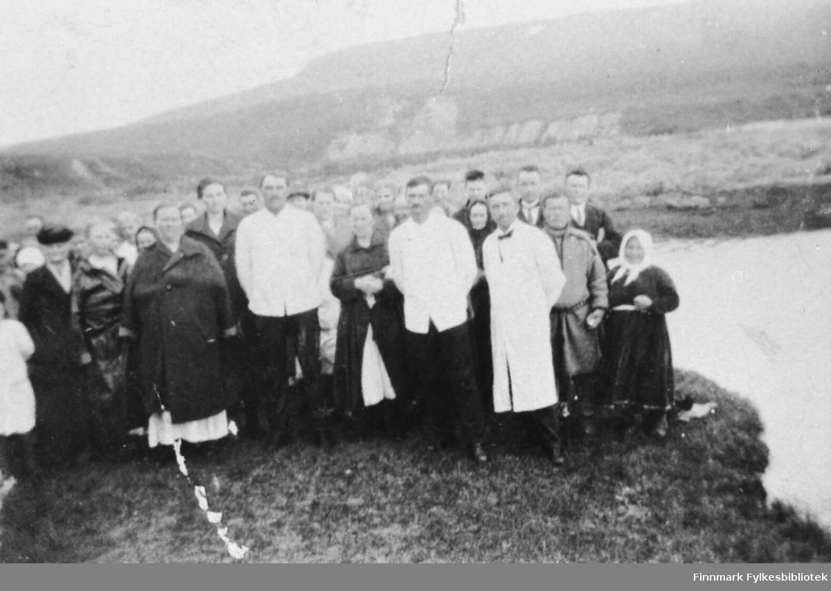 Voksendåp i Jakobselv. En gruppe mennesker samlet ved elvaen, en del av dem kledd i hvite kapper. Ytterst til høyre står paret Mikkel og Anna Hallonen, kalt Mikkas-Anna. De andre er ukjent.