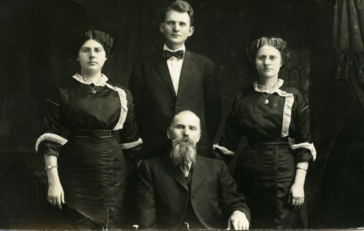 Portrett av to menn og to kvinner. Kvinnene er iført mørke kjoler og mennene er iført dress. En av dem har også sløyfe.