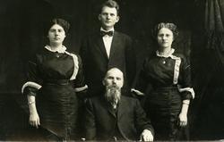Portrett av to menn og to kvinner. Kvinnene er iført mørke k