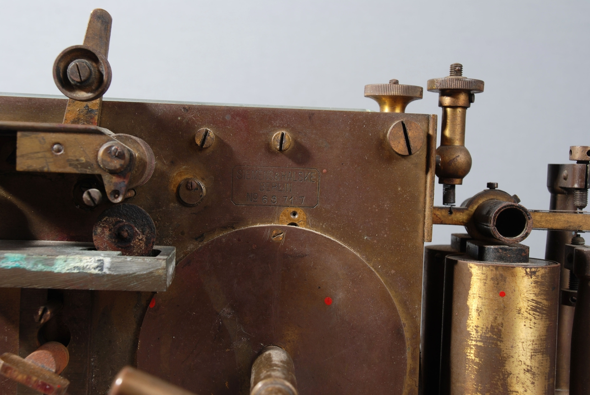 Maskin for mottak av signal fra offentlig (og privat) brannmelder. Den registrerte nummer på brannmelder med streker på papirstrimmel plassert i egen skuff på undersiden av apparetet. a)er en trekasse påmontert metallmaskin, messinghendel på siden. På toppen av metalldelen et rektangulært glass. Et rundt glassvindu på grunnplaten viser papirstrimmel.  b) Treskuffefront ømed metallhåndtak, rundt messinghjul med papirstrimmel rull festet på. Brukt av sambandsvakt på hovedstasjon og Sandviken stasjon.