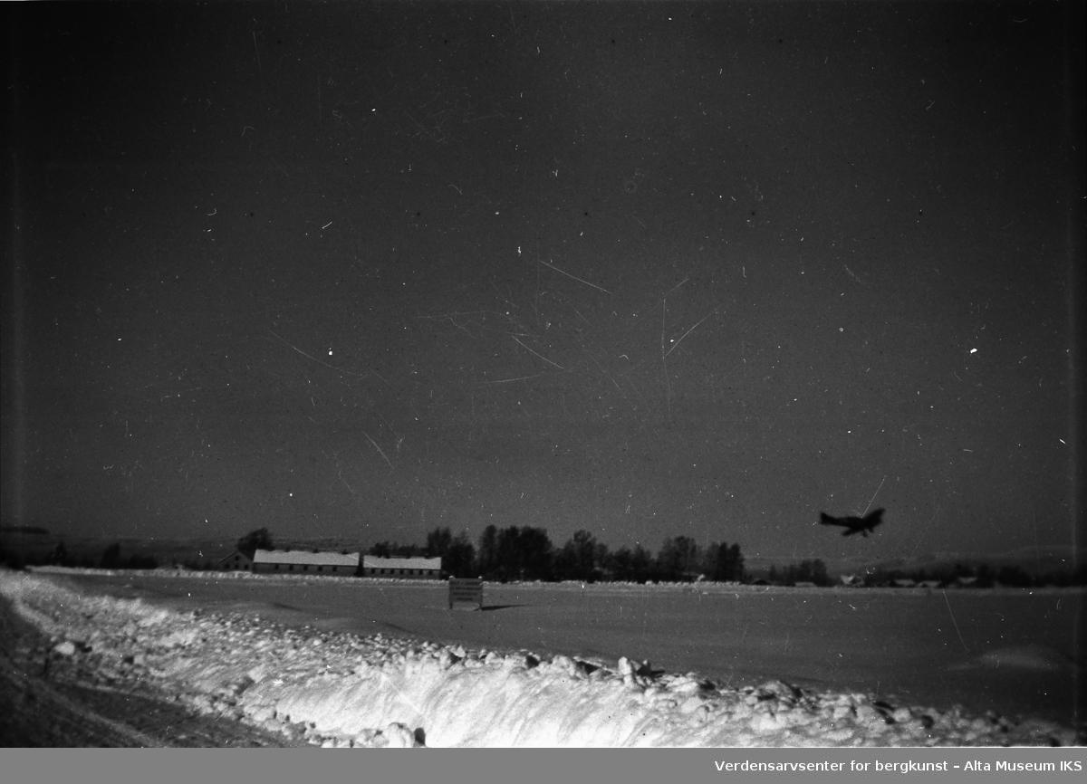 Bilde av et fly som flyr lavt over bakken om vinteren.