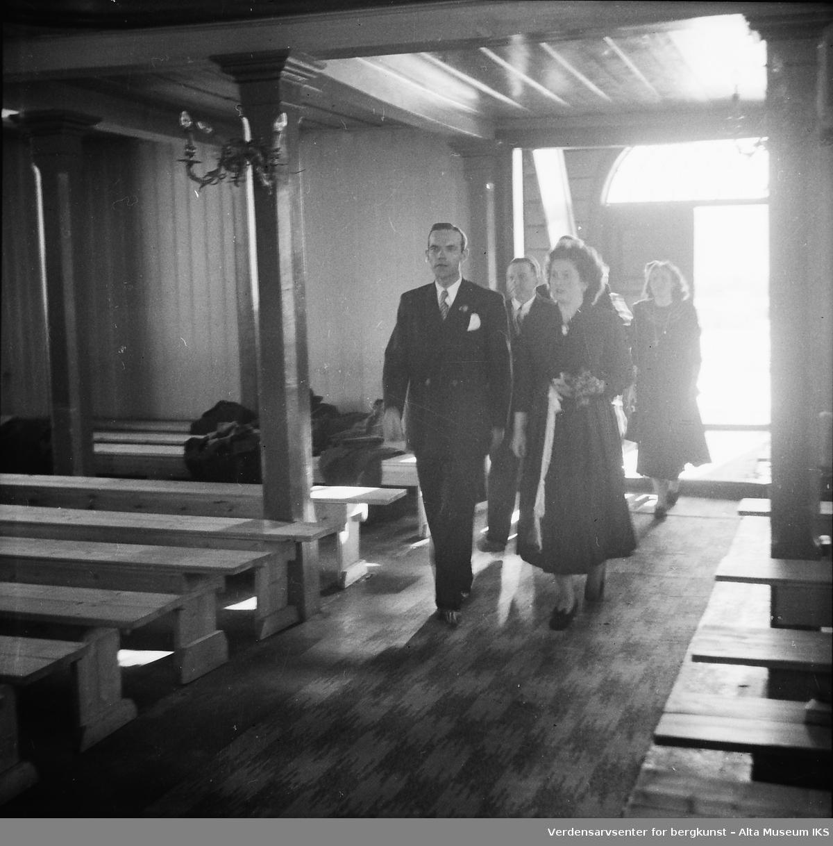 Brud og brudgom går ned kirkegangen mot alteret.