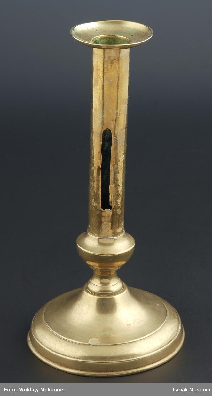 Form: rund,svakt profilert fot og stett,ovenfor er stetten rett og glatt,på stetten rektangulær åpning til reguleringsskrue