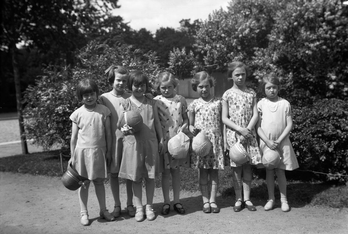 """Sju flickor utanför """"Bostäderna"""" i Torgparken, vid nuvarande Olof Palmes plats vid Västra torget, Jönköping. Från vänster Elsa Emanuelsson? (1), Britta Emanuelsson (2), Britta Blomkvist (3), Asta Johansson (4), Lilian Ekelund (5), Ingrid Ekelund (6), Anna-Lisa Fransén? (7)"""