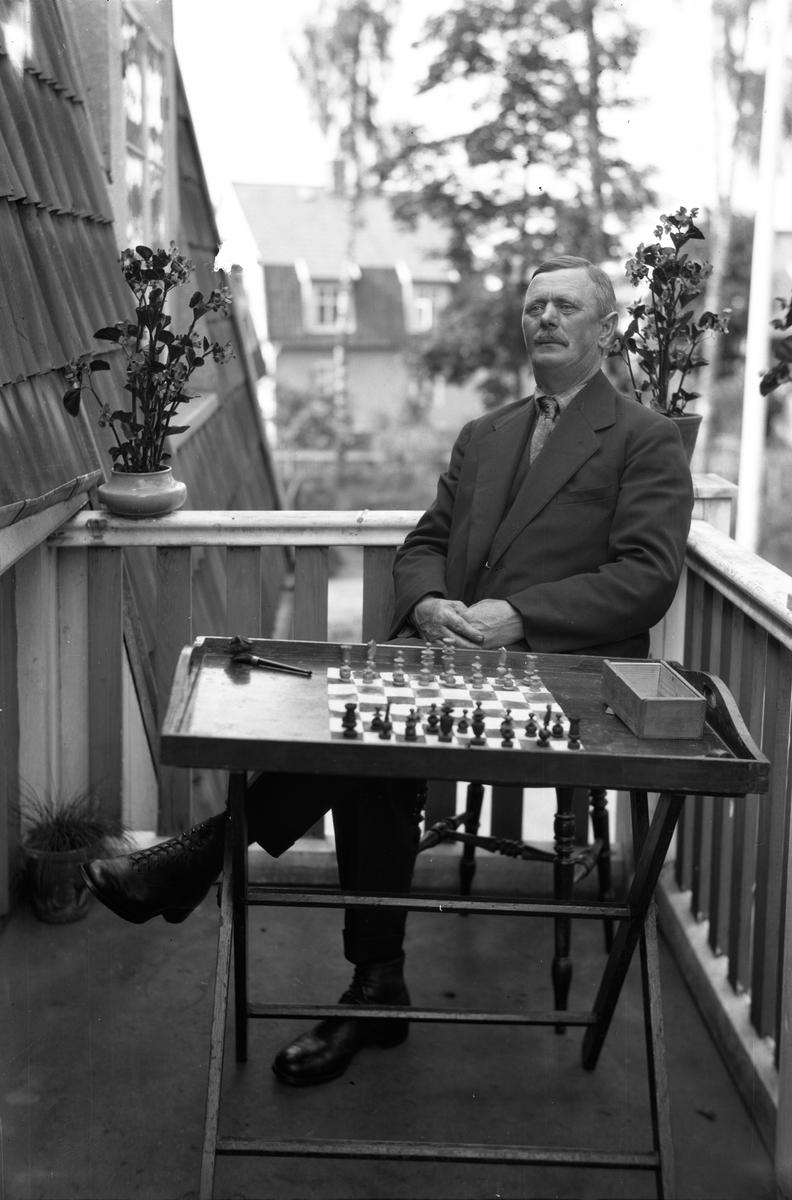 Ernst Holmgren sitter på sin balkong på Presidentgatan 23 i Jönköping. På bordet bredvid sig har han ett schackbräde. Han föddes 6/3 1873 och fick sju barn. Han arbetade först som grovarbetare, därefter som stensättare, var bl.a. med och byggde teatern. Han hade sju barn.Han brukade sjunga och joddla på gatorna.