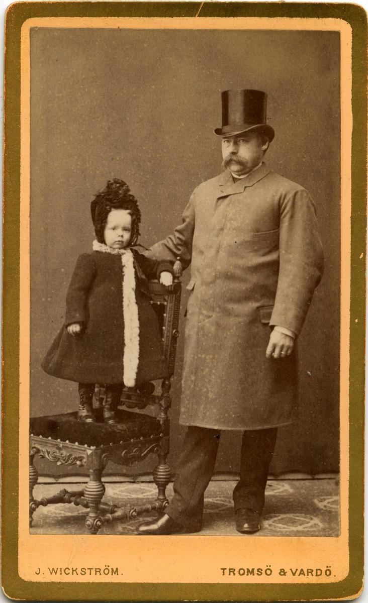 En mann i frakk og flosshatt står ved siden av et barn på en stol. Begge er ukjent.