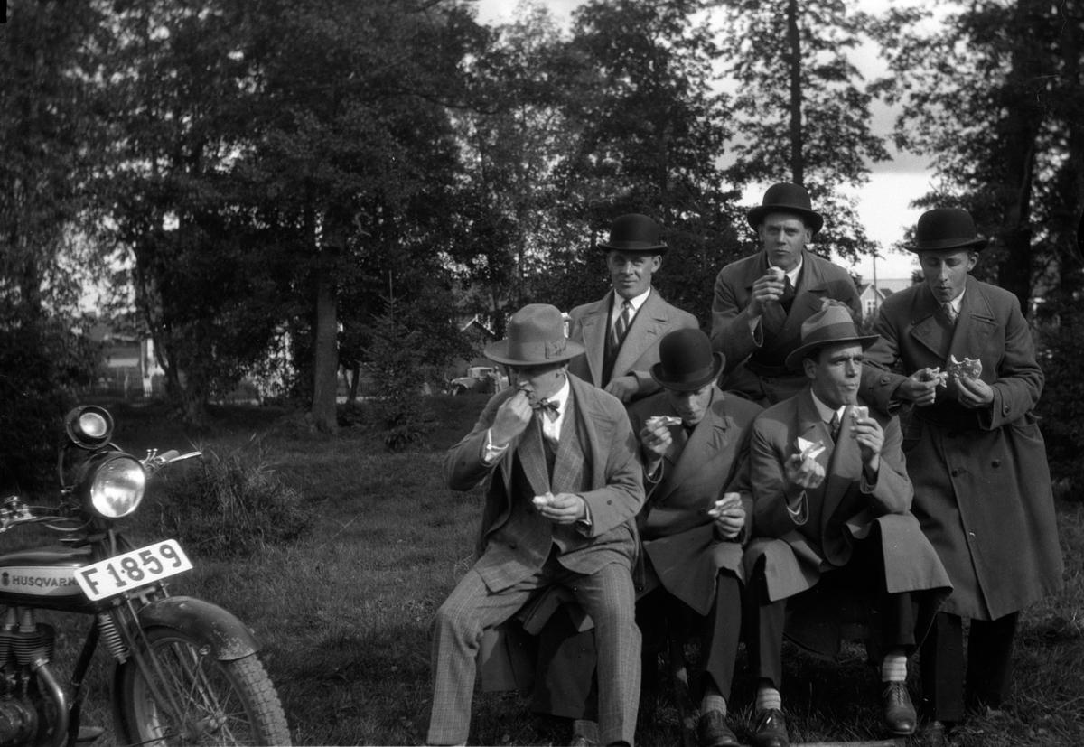 """Några män från föreningen Tord tar matpaus och de äter kokt korv i papper och bröd i andra handen. Till höger sitter Einar Svensson och i mitten upptill står """"Nisse Falköping"""". En Husqvarna motorcykel står parkerad bredvid dem."""