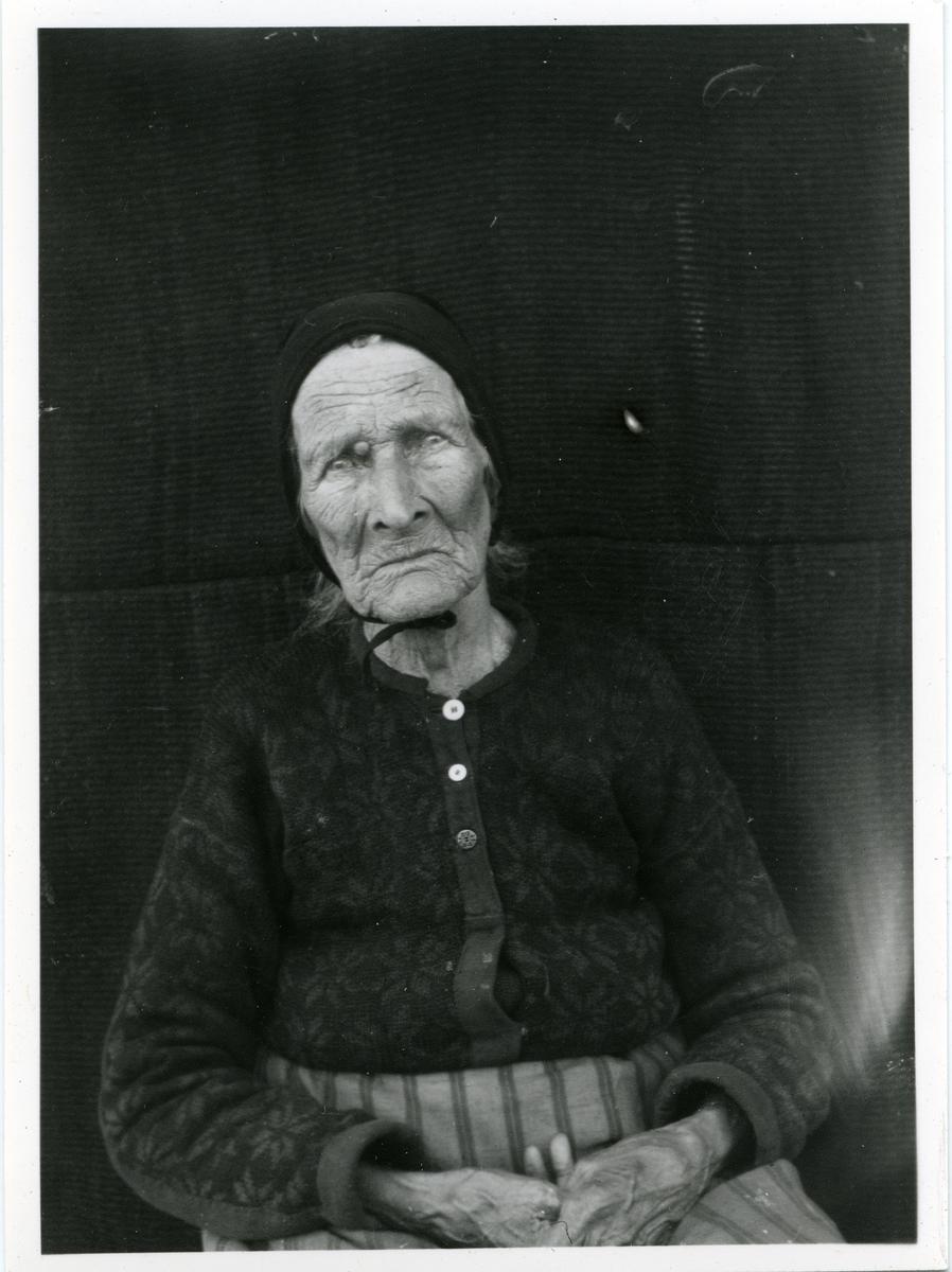 Portrett i halvfigur av eldre dame. Hun er kledd i strikkejakke og forkle og har en lue/kyse på hodet.