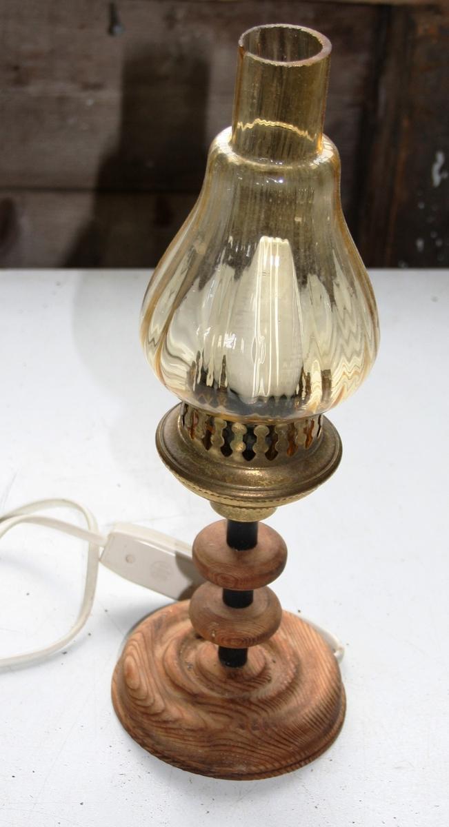 Liten elektrisk bordlampe med rund fot og gjennomsiktig laus glaskuppel med messingfarga blikkhaldar