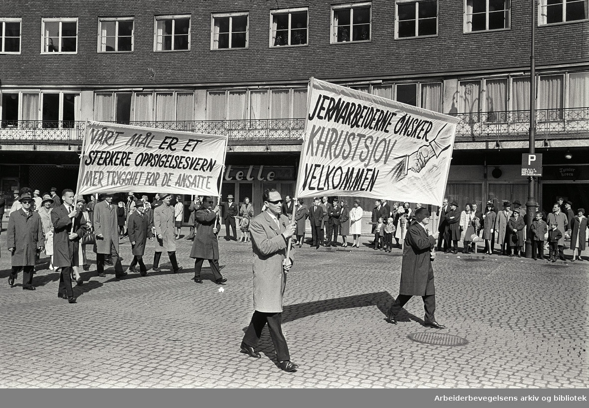 1. mai 1964 i Oslo.Demonstrasjonstoget ved Rådhusplassen.Parole: Jernarbeiderne ønsker Khrustsjov velkommen.Parole: Vårt mål er et sterkere oppsigelsesvern.Mer trygghet for de ansatte