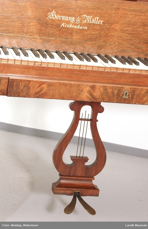 Form: rekt. 4 balusterformede ben påsatt trinser, lyreformet pedalfeste