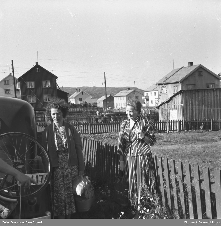 Jenny Drannem og Synnøve Vorren fotografert ved en bil. Begge har en veske i hånda. Man ser i bakgrunnen gjenreisningshus. Stedet er Kirkenes