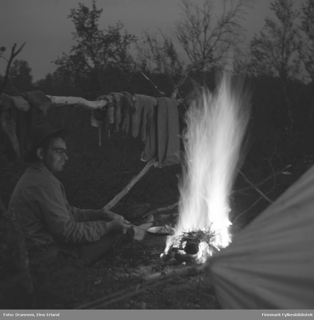 Asbjørn Gabrielsen sitter ved bålet og steker mat på bålet