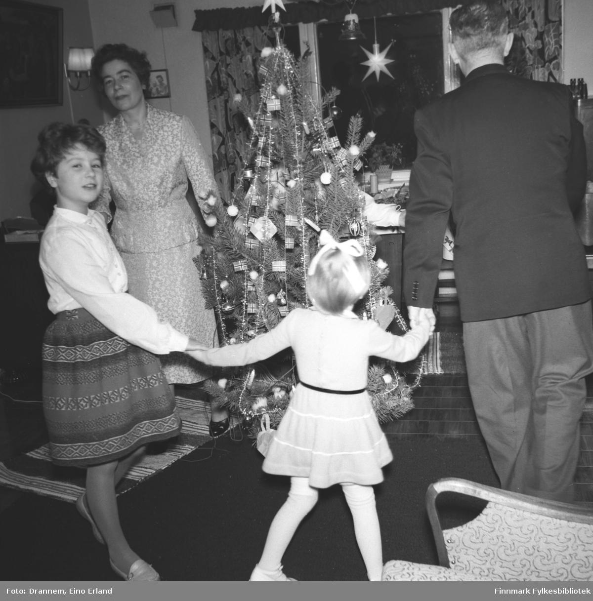 Jenny Drannem og Turid Lillian med noen medlemmer av familien Sørensen går rundt juletreet