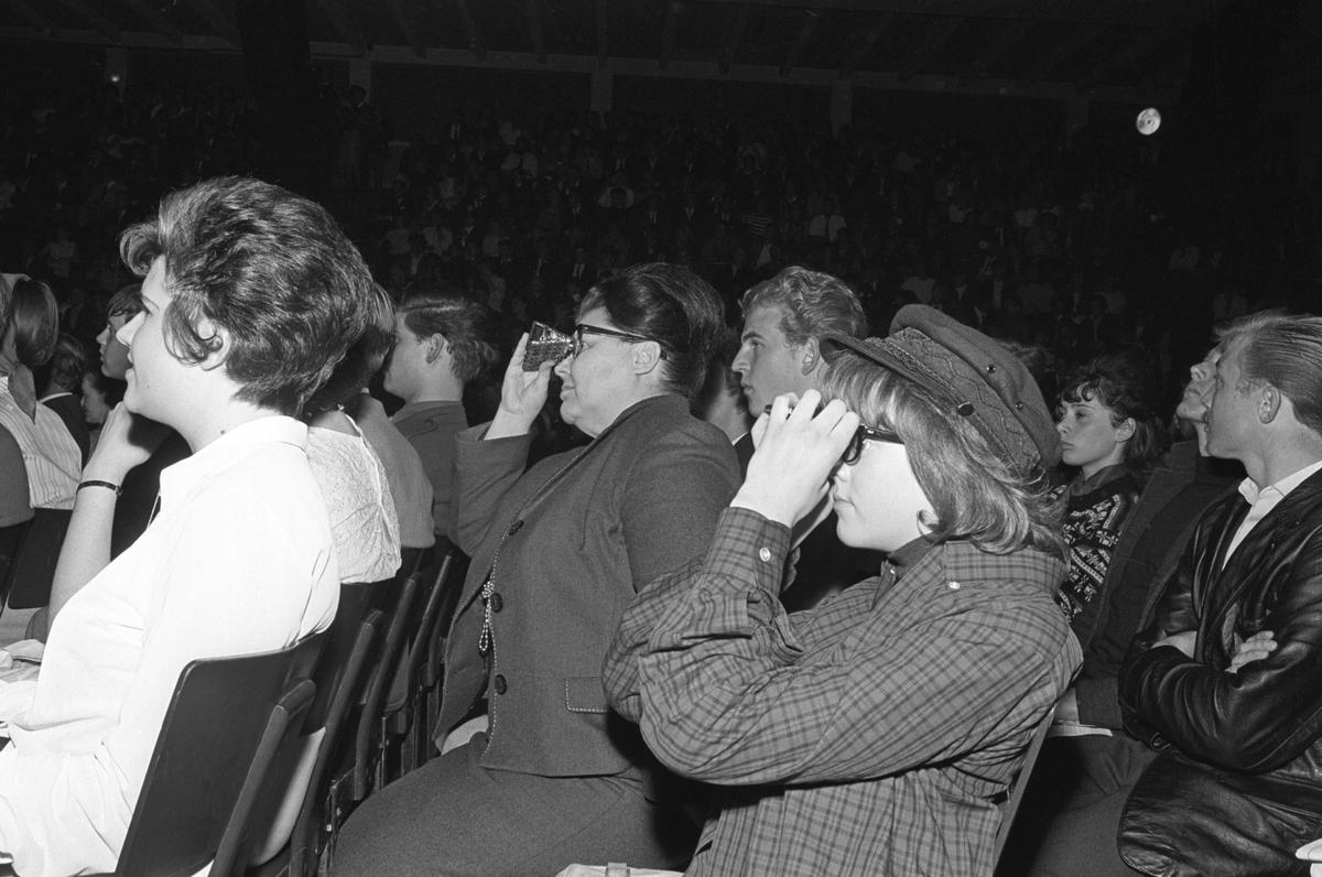 Konsert med det engelske bandet The Beatles i K.B. Hallen i København. Publikum i alle aldre. Noen bruker kikkert.