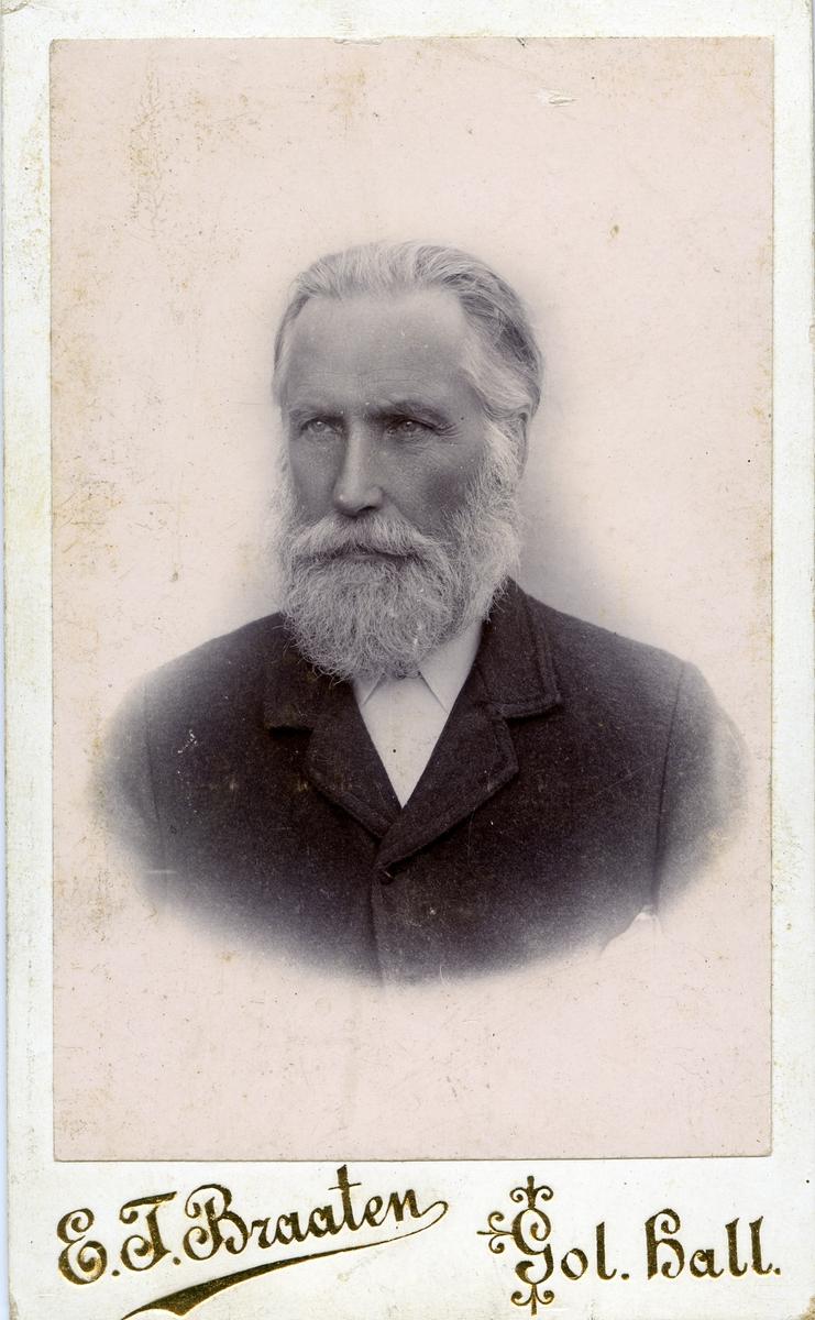 Portrett av eldre mann med helskjegg. Mannen er iført hvit skjorte med mørk jakke over.