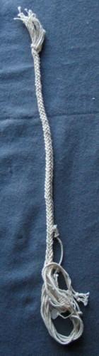 Makraméprov. Flätad fyrkantig snodd. Börjar med en ögla av två trådar i ena änden och har lösa trådar från den oavslutade flätan i den andra. Flätad med åtta trådar av ett oblekt bomullsgarn ihoptvinnat av tre delar där varje del i sin tur består av sju enkla trådar.