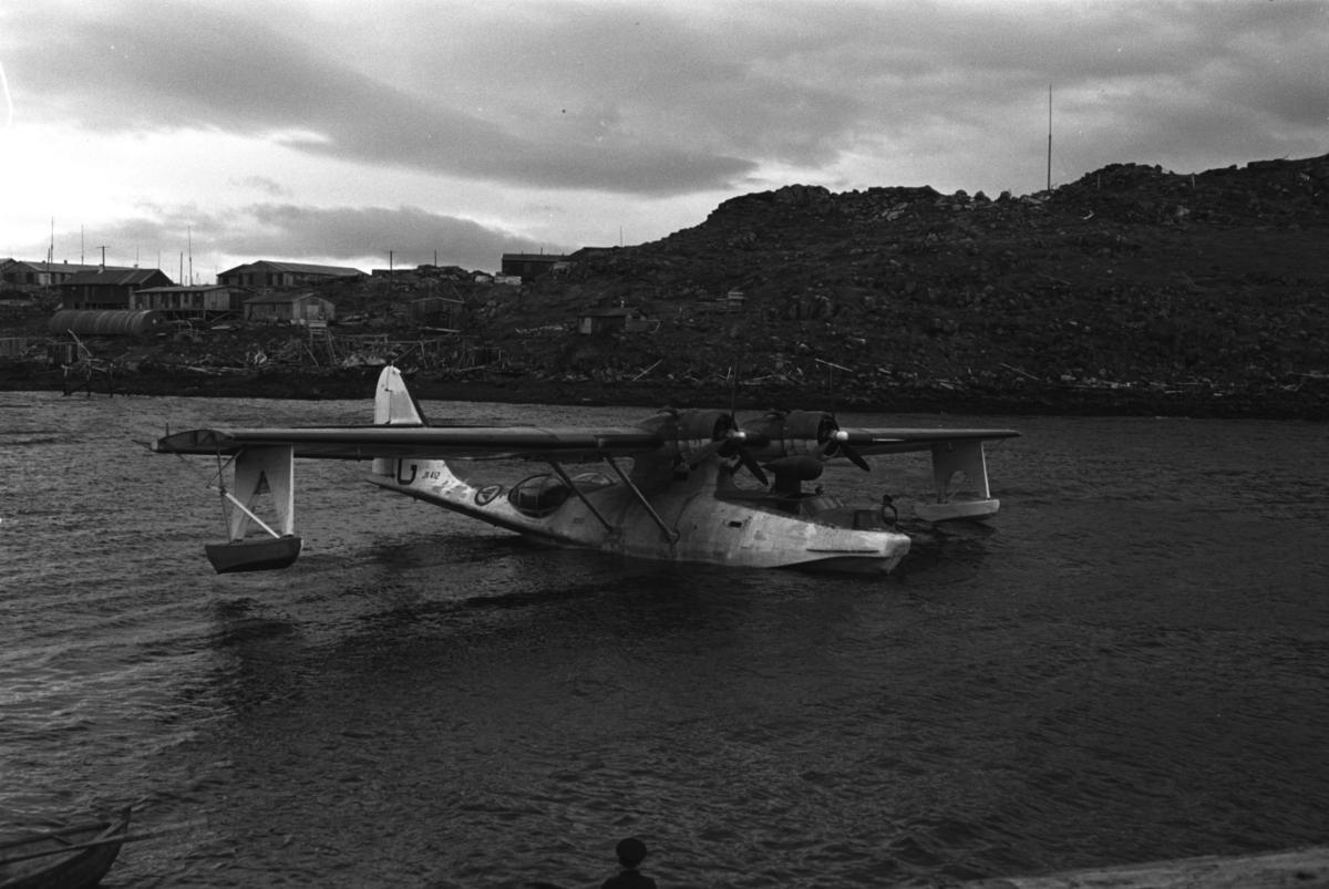 """En flybåt av merket Catalina Mk IVB har landet i Honningsvåg like etter andre verdenskrig. På halepartiet kan en lese JX 412 og en stor G,( KK-G). Flyet fikk ny bokstavkode i løpet av 1946 til K-AK. Ifølge fotografen er bildet tatt i 1946 med gammel bokstavkode G som bildet viser. er et fly som starter og lander på sjøen.   En flybåt skiller seg fra et sjøfly ved at selve skroget flyter på vannet, skroget er dermed formet som på en båt. Eksempler på flybåter er for eksempel Short Sandringham og Dornier Do X. Flybåtene var svært populære før nettet av flyplasser var skikkelig utbygd, og egnet seg bedre for langdistanseflygninger enn samtidige landbaserte passasjerfly.  Arkitekt Ola Hanche-Olsen arbeidet ved Brente Steders Reguleringskontor i 1946. Hovedadministrasjon for gjenreisning av Nord-Troms og Finnmark ble lagt til Harstad og fikk navnet Finnmark kontoret. Landsdelen Nord-Troms og Finnmark blev oppdelt i syv distrikt med hver sin administrasjon. Honningsvåg, distrikt IV, skulle betjene Nordkapp, Lebesby, Porsanger og Karasjok kommune.  Ola Hanche-Olsen har tatt bildene. Han var født 13. mars 1920 i Borre, død 11. februar 1998 i Gjettum. Han var både arkitekt og barnebokforfatter. Han hadde artium fra 1939, arkitekteksamen fra NTH 1946 og arbeidet deretter ved Finnmarkskontoret 1946–48 før han etablerte egen arkitektpraksis. Han debuterte som barnebokforfatter i 1974 med lettlest-boka """"Knut og sjørøverne"""", og skrev i alt 12 bøker. Han var XU-agent 1944-45, og var også en aktiv fjellklatrer og friluftsmann. Ola var gift med Solveig Hanche-Olsen (f. Falkenberg); de fikk 3 barn, blant dem matematikeren Harald Hanche-Olsen."""