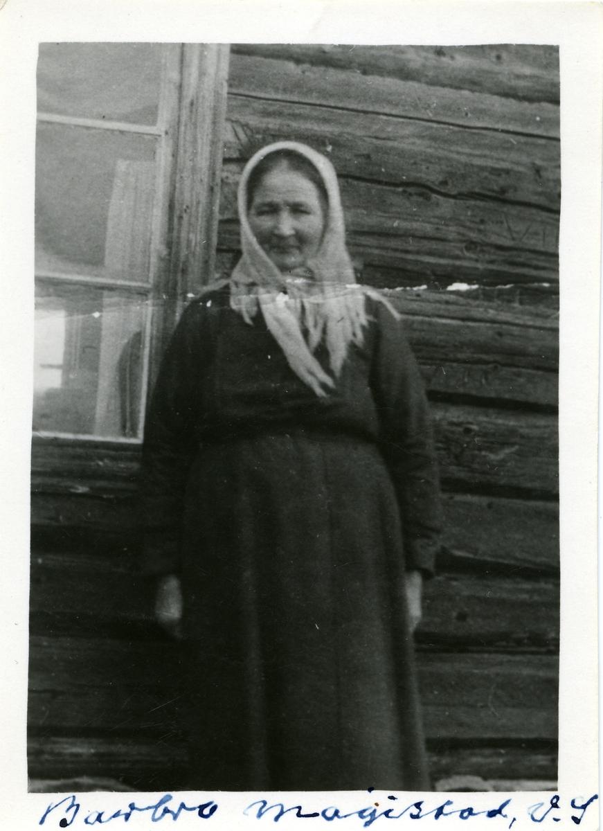 Portrett av kvinne stående foran et vindu. Kvinnen er iført skaut og svart kjole.
