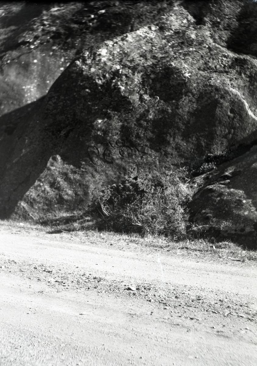 En grusvei som fører opp mot et hus. I forgrunnen ligger en sykkel veltet opp mot berget.