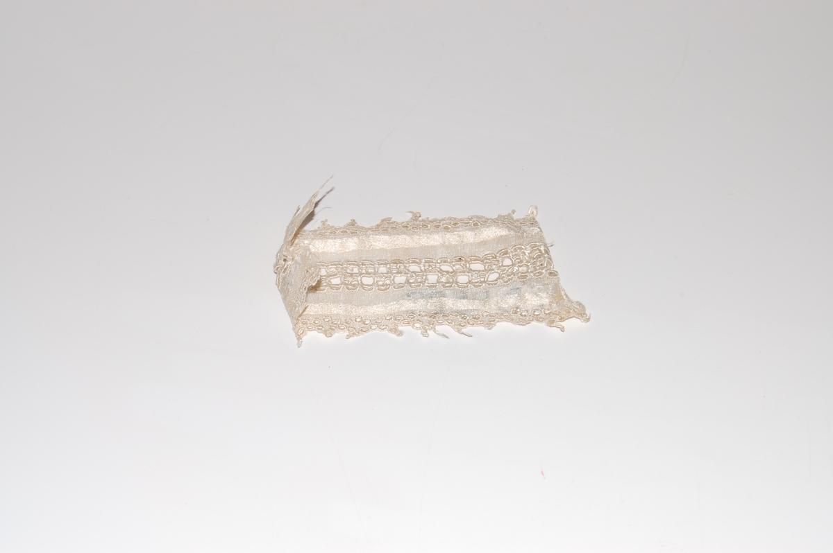 Form: sirkel med løkke/oppheng, tredt inn silkebånd og sløyfe på toppen