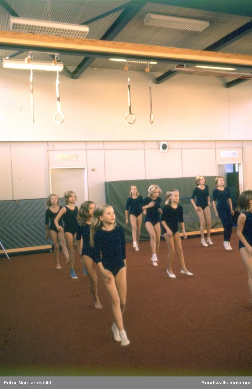 Gymnastiklektion på Nackstaskolan. Större delen av flickorna har tidstypisk klädsel i form av sockiplast och mörkblå gymnastikdräkt.