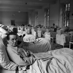 Paris. Äldre kvinna med sammanbiten min i sjukhussäng.